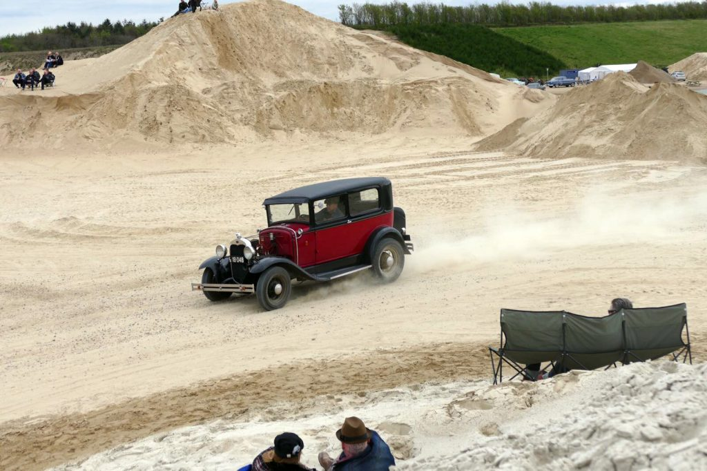 1930s Ford Model A speeding round a gravel race track